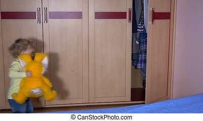 Playful boy with bunny friend hiding in wardrobe. Static...