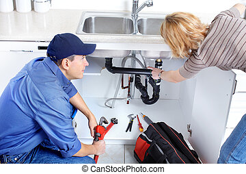 plumber - Mature plumber fixing a sink at kitchen