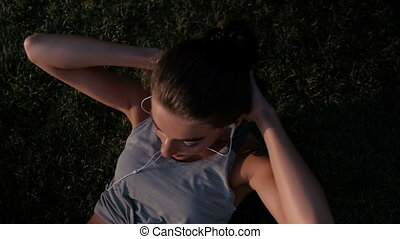 Woman lying on the lawn swinging the press in the headphones.