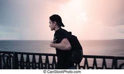 Tourist Man with Backpack Walking on Beach by Sunset Sea