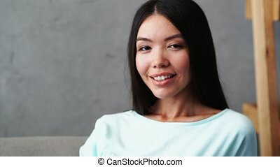 Cheerful young woman smiling at home