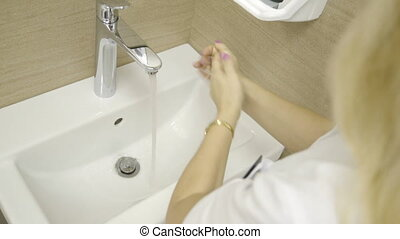 Beautician woman washing her hands before procedure in...