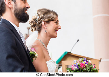 Bride and groom having wedding in church at altar with...