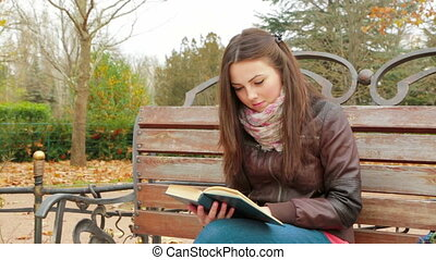 Young Girl Is Reading A Book In Park