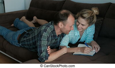 A man and a woman make joint notes in a notebook lying on...