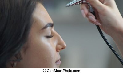 Airbrush professional makeup - Female make-up artist apply...