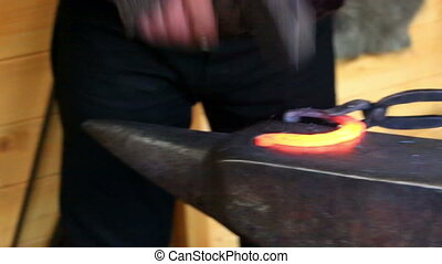 Blacksmith at work - Blacksmith forges a horseshoe on the...