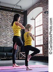 Mother and daughter wearing sports clothing practicing yoga...