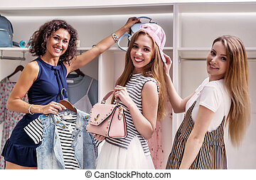 Happy funny female friends picking new clothes and...