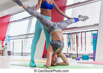 Fit young woman performing yoga headstand leg split with the...