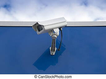 Security camera on the side of a blue building