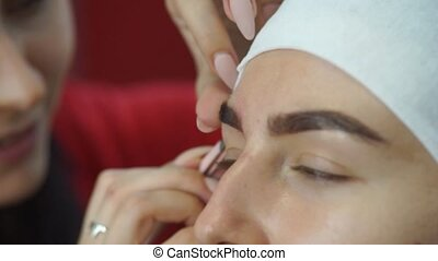 A young woman plucking eyebrows with tweezers. - The master...