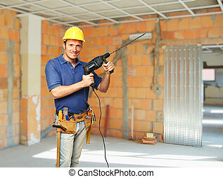 handyman portrait - confident handyman with big drill on...