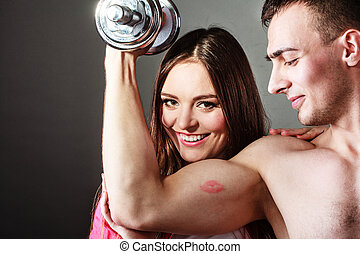 Couple muscular man and girl admiring his strength. -...