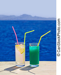 Two cocktails on marble table at beach - travel background