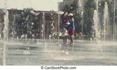 Young happy couple dancing in the fountain - Slow motion....