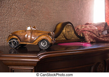 Toy homemade retro car and clock on an antique chest of...
