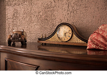 Antique desk clock and auto on the chest of drawers near the...