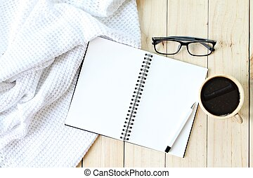 Flat lay of white knitted blanket, eyeglasses, cup of coffee and blank notebook paper on wooden background