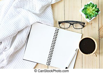 Flat lay or top view of white knitted blanket, eyeglasses, cup of coffee and blank notebook paper on wooden background