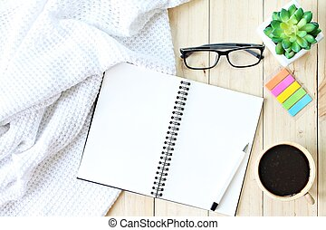 Flat lay or top view of white knitted blanket, open blank notebook paper, coffee cup and eyeglasses on wooden background