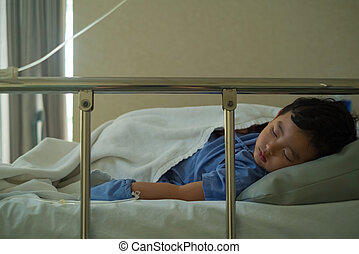 Sick Asian kid boy 2 years old lying sick in hospital bed.