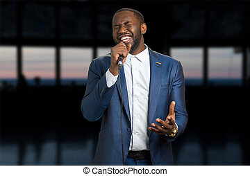 Singing man on the evening background. Darkskinned man with...