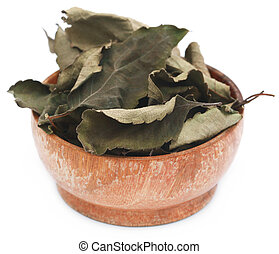 Dry holy basil or tulsi leaves in a wooden bowl