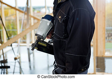 Midsection Of Carpenter Holding Drill Machine At Site - Side...