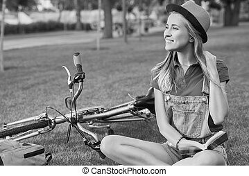 Young woman reading a book after cycling at the local park -...