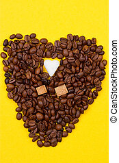 Coffee beans and sugar in the form of heart on a yellow...