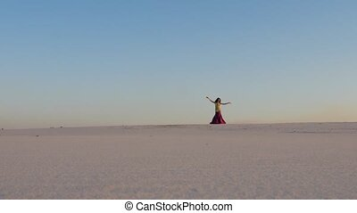 Dancer against the sky dancing belly dance in a brilliant...