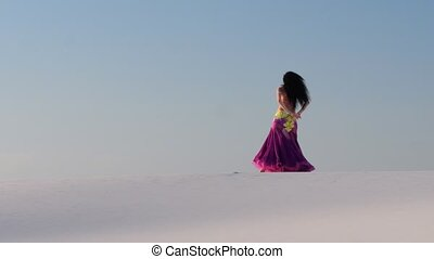 Girl dances belly dancing in the sandy desert, her movements...