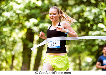 Young woman running the race crossing the finish line.