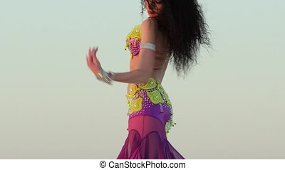 Brunette dances against the sky a belly dance, she is...
