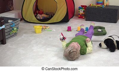 little cute girl lie on white carpet between toy in her...