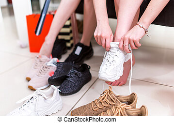 Cropped image of teenage girls trying on sports shoes in a...