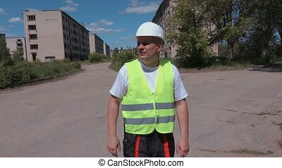 Builder talking with guests near abandoned apartment houses