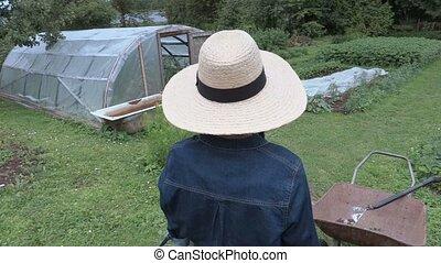 Camera follows female gardener near pots