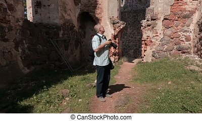 Man with photo camera in old castles ruins