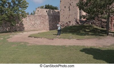 Tourist with photo camera in the castle yard
