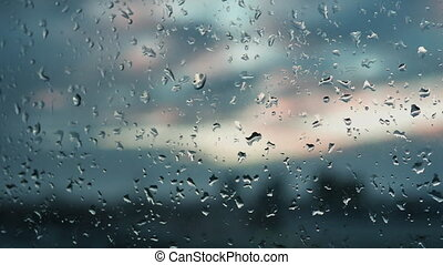 Raindrops on a window. Outside, the view of the city. Sunset and clouds. Melancholy