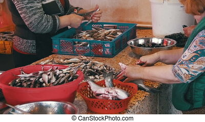 Woman Fish Seller Cleans and Cutting Fresh Fish in Fish...