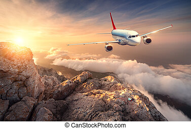 Airplane is flying over clouds at sunset. Landscape with...