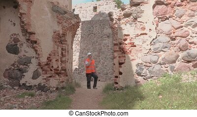 Builder surveyed the ruins of an old castle