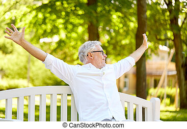 happy senior man sitting on bench at summer park - old age,...