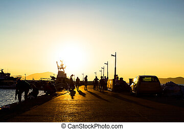 Silhouetted shot of a people fishing on pier at sunset -...