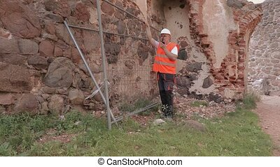 Builder using walkie talkie near fence