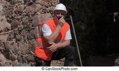 Builder on walkie talkie near fence