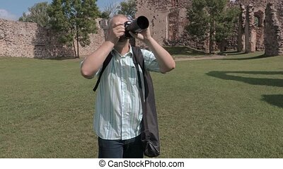 Tourist take pictures on photo camera in the castle yard